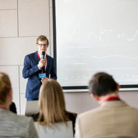 Confident businessman giving presentation in seminar hall at convention center